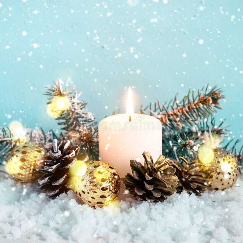 Bożenarodzeniowy błękitny skład Płonąca świeczka, conifers i rożki na śnieżnym tle, zdjęcia stock