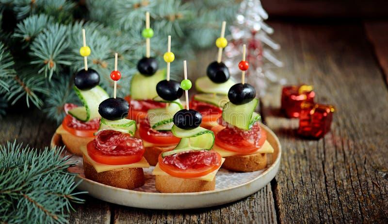 Bożenarodzeniowy canape na skewer od chlebowego baguette z serem, kiełbasą, pomidorem, ogórkiem i oliwkami grzanki, Tradycyjna pr obraz royalty free