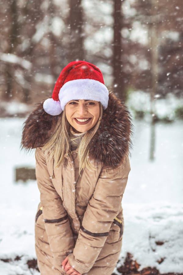 Bożenarodzeniowy czas - dziewczyna z Santa zimy śniegu kapeluszowym dniem zdjęcia royalty free