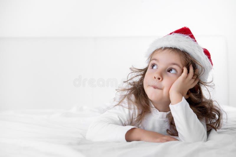 Bożenarodzeniowy czas, mała dziewczynka w Święty Mikołaj kapeluszowym główkowaniu o prezentach i teraźniejszość, fotografia stock