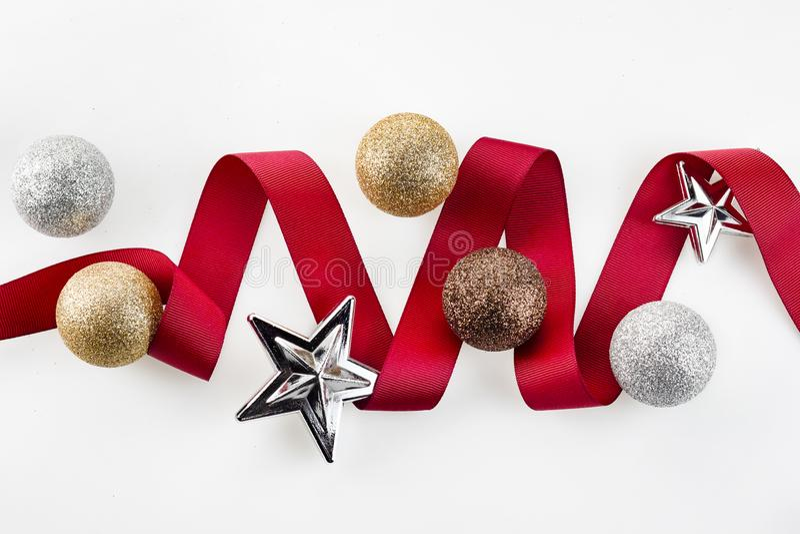 Bożenarodzeniowy czerwony faborek dekoruje z srebnymi błyskotliwość ornamentu piłkami i gwiazdą na białym tle zdjęcie stock