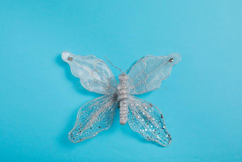 Bożenarodzeniowy dekoracji srebra motyl na błękitnym tle obraz royalty free