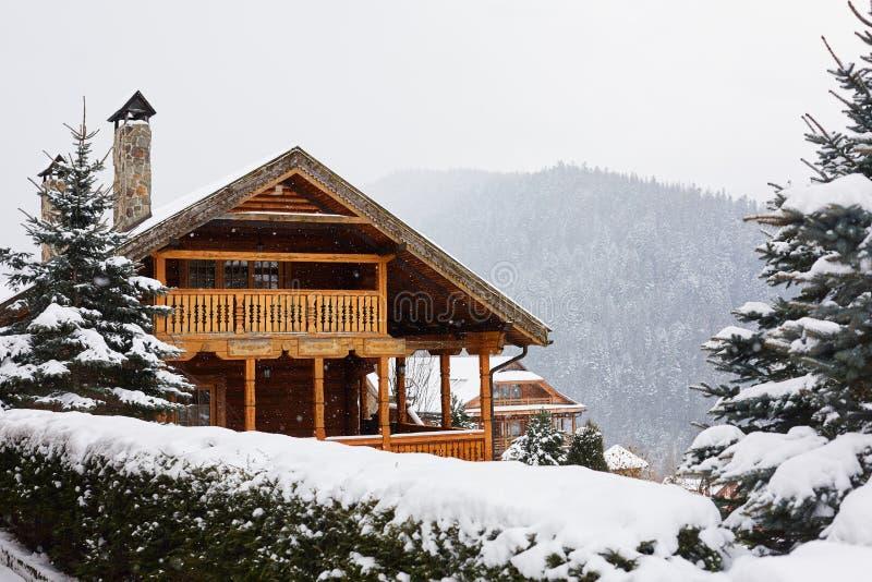 Bożenarodzeniowy drewniany dwór w górach na opad śniegu zimy dniu Wygodny szalet na ośrodku narciarskim blisko sosnowej lasowej c obrazy stock