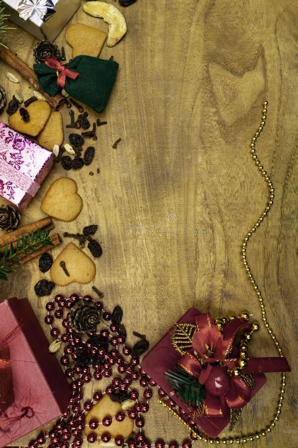 Bożenarodzeniowy drewniany tło Bożenarodzeniowi miodowniki, rodzynki, imbir, kardamon, cloves, cynamonowi piernikowi dekoracyjni  obraz stock