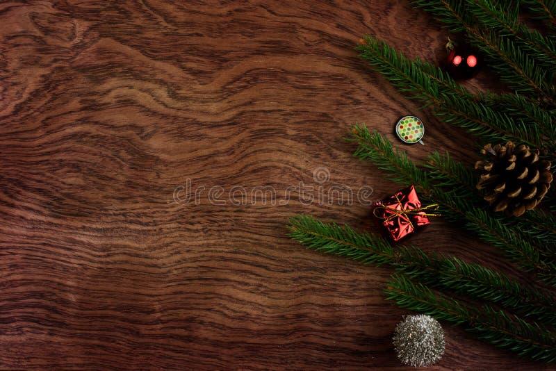 BOŻENARODZENIOWY JEDLINOWEGO drzewa tło NA DREWNIANYM biurku Z sosna rożkiem, sferami, CZERWONYM prezentem I NIEKTÓRE dekoracją, obrazy stock