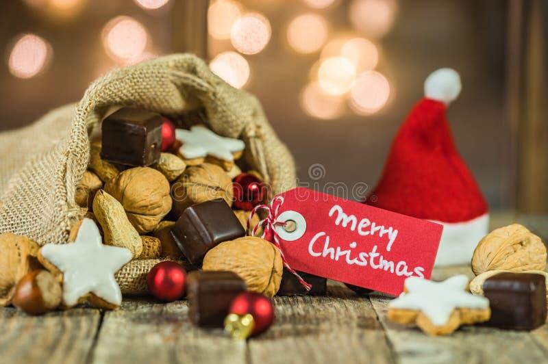 Bożenarodzeniowy jedzenie i cukierki z czerwonym Santa kapeluszem i z etykietka teksta Wesoło bożymi narodzeniami fotografia stock