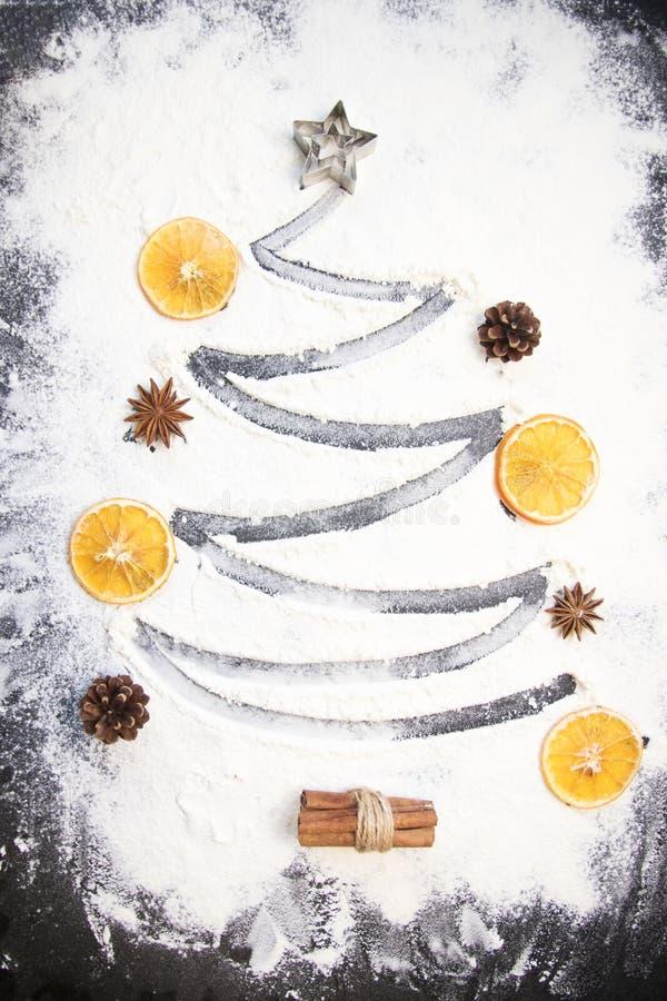 Bożenarodzeniowy kucharstwo: jedlinowy drzewo robić od mąki na ciemnym stole, składnikach dla piec i suszyć owoc, na ciemnym tle obraz stock