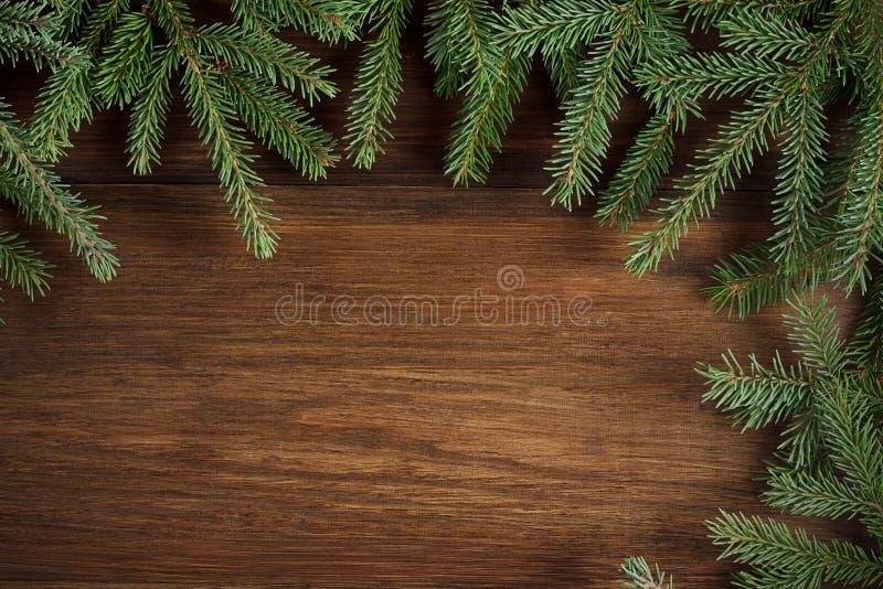 Bożenarodzeniowy nieociosany drewniany tło z wiecznozielonymi gałąź zdjęcia royalty free