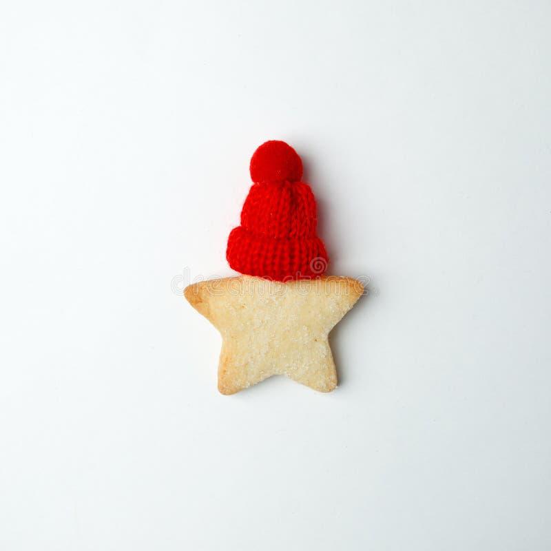 Bożenarodzeniowy nowego roku świętowania dekoracji pojęcie, imbirowa chleb gwiazda z dekoracyjnym czerwonym kapeluszem na białym  fotografia stock