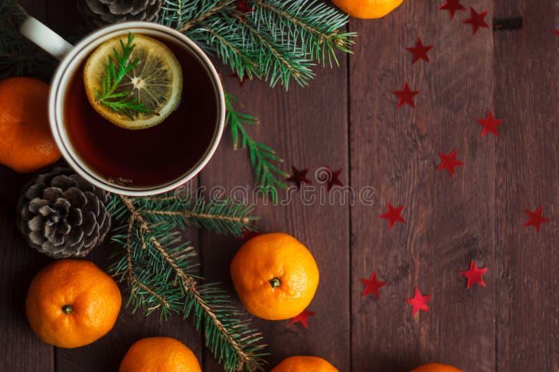 Bożenarodzeniowy nowego roku tło z tangerines, herbatą i cukierkami na stole, Zima wciąż Selekcyjna ostrość obrazy stock