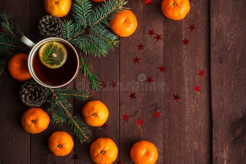 Bożenarodzeniowy nowego roku tło z tangerines, herbatą i cukierkami na stole, Zima wciąż Selekcyjna ostrość obrazy royalty free