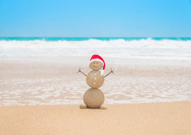 Bożenarodzeniowy piaskowaty bałwan w Santa kapeluszu przy tropikalną plażą obraz stock