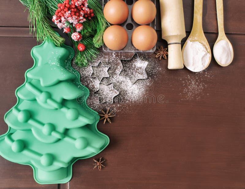 Bożenarodzeniowy pieczenie torta tło Składniki i narzędzia dla piec - mąka, jajka, krzem foremki w formie choinki, zdjęcia stock