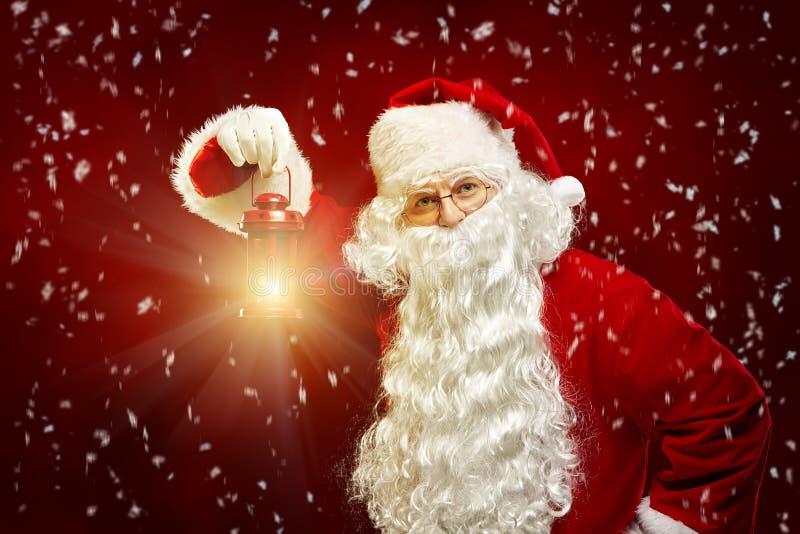 Bożenarodzeniowy pojęcie Święty Mikołaj z lampionem w jego ręce na r obraz stock