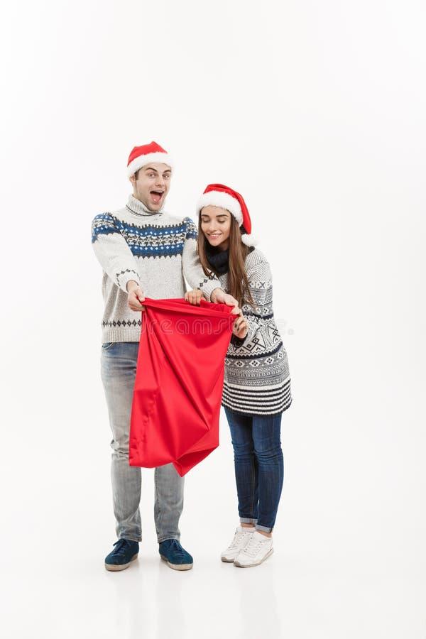 Bożenarodzeniowy pojęcie - Folująca długości Młoda atrakcyjna para trzyma Santa torbę odizolowywająca na bielu popielatym tle zdjęcie stock