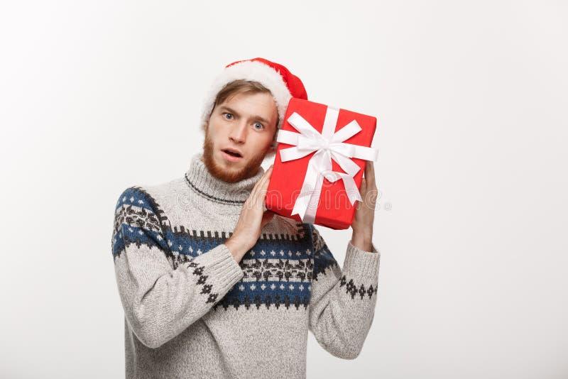 Bożenarodzeniowy pojęcie - Szczęśliwy ciekawy młody człowiek z brodą niesie teraźniejszość i słucha inside pudełko odizolowywał n obrazy stock
