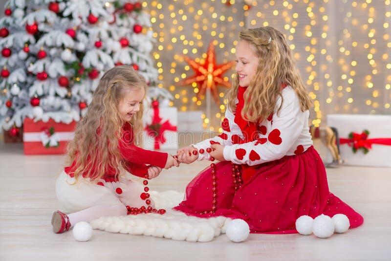Bożenarodzeniowy portret dwa beautyful ślicznej dziewczyny Uśmiecha się siostra przyjaciół i xmas luksusu zieleni białego drzewa  obraz stock