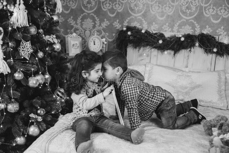 Bożenarodzeniowy portret mali dzieciaki siedzi na łóżku z teraźniejszość pod choinką Chłopiec całuje dziewczyny chłopiec wakacji  zdjęcia royalty free