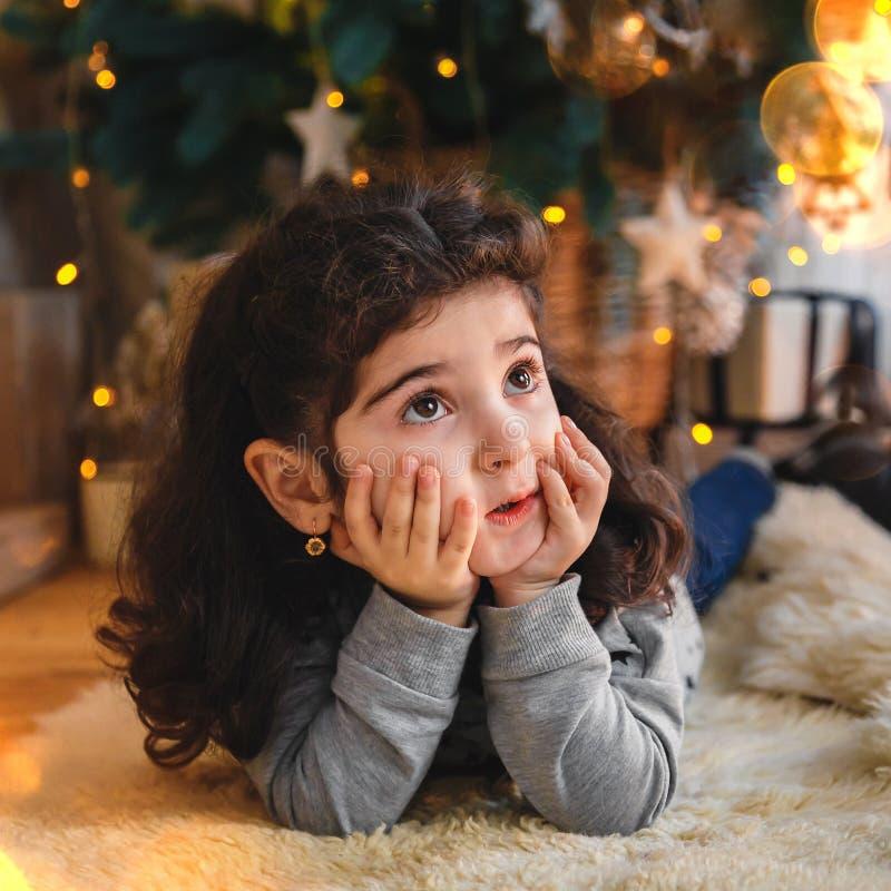 Bożenarodzeniowy portret piękny małej dziewczynki lying on the beach na podłoga pod choinką Zima wakacje nowego roku i Xmas pojęc obraz stock