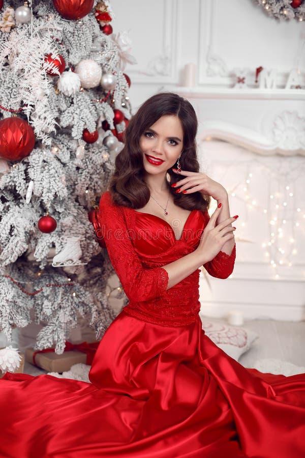 Bożenarodzeniowy portret szczęśliwa uśmiechnięta dziewczyna w czerwieni sukni obsiadaniu śnieżnym xmas drzewem, brunetka z czerwo fotografia royalty free
