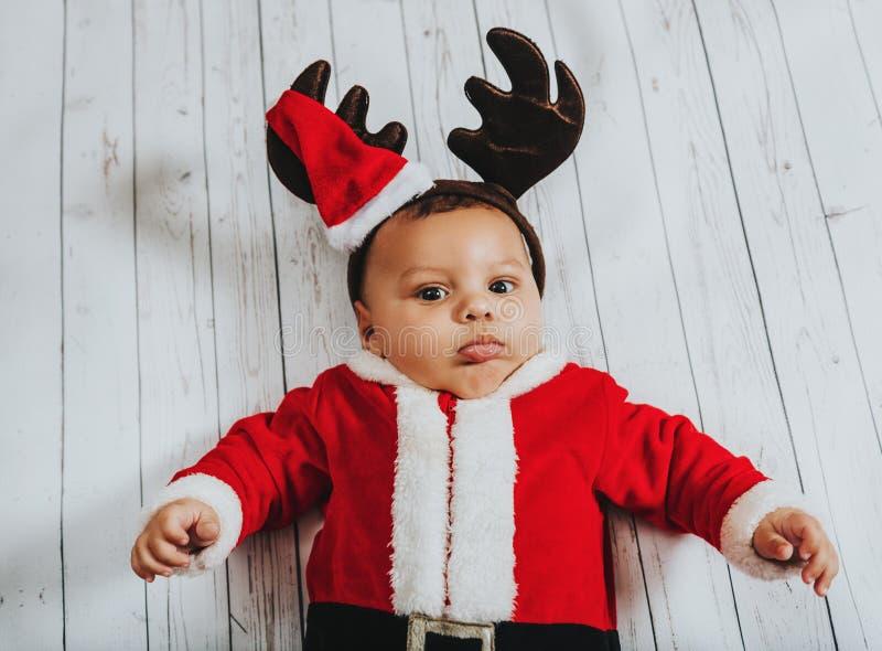 Bożenarodzeniowy portret uroczy nowonarodzony dziecko jest ubranym Święty Mikołaj ` strój obrazy royalty free