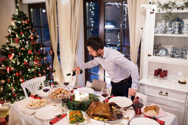 Bożenarodzeniowy posiłek kłaść na stole Obsługuje dolewania wino w szkła zdjęcia royalty free