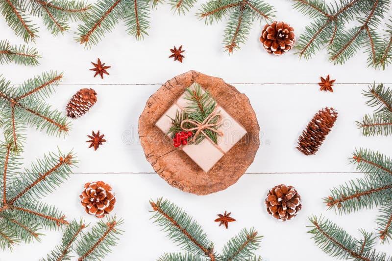 Bożenarodzeniowy prezent na fiszorku na białym drewnianym tle z jodłą rozgałęzia się, sosnowi rożki, czerwone dekoracje Xmas i sz zdjęcia stock