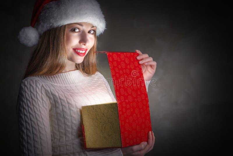 Bożenarodzeniowy prezent. Szczęśliwy dziewczyny otwarcia pudełko obraz royalty free