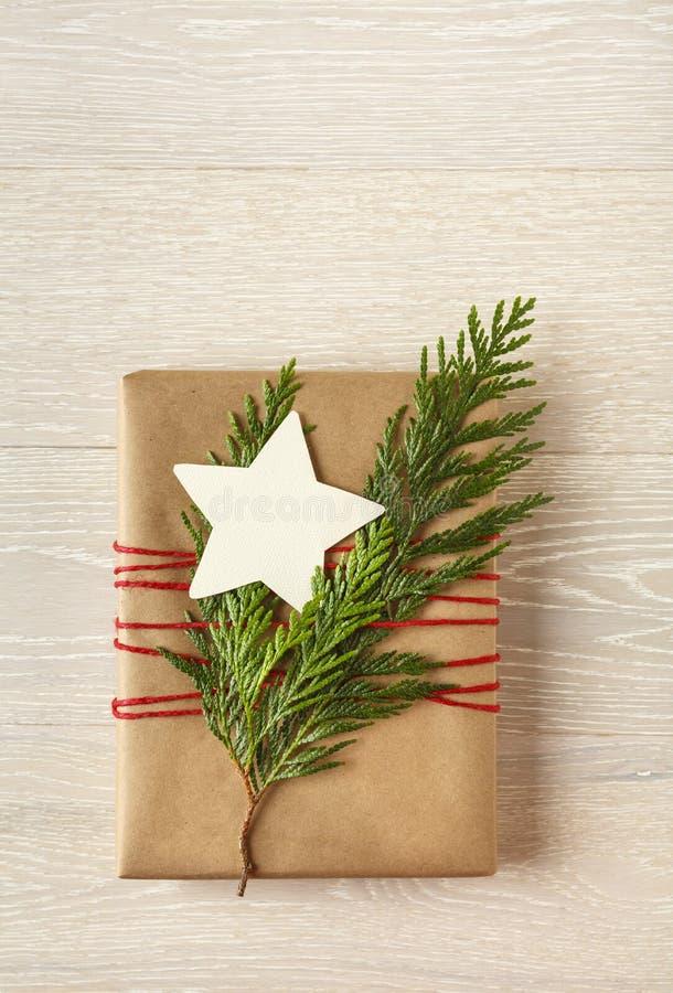 Bożenarodzeniowy prezent teraźniejszy z przetwarzającym opakunkowym papierem i naturalnymi dekoracjami na nieociosanym drewnianym zdjęcia stock