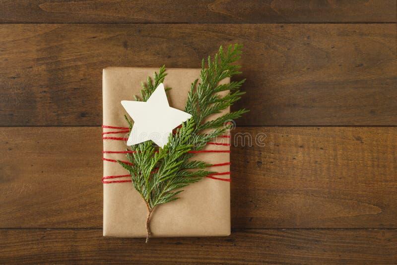 Bożenarodzeniowy prezent teraźniejszy z przetwarzającym opakunkowym papierem i naturalnymi wiecznozielonymi dekoracjami na drewni zdjęcie royalty free