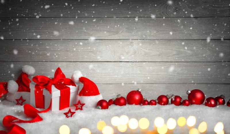 Bożenarodzeniowy prezent w śniegu, drewniany tło obrazy stock