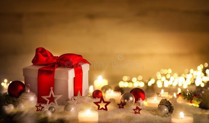 Bożenarodzeniowy prezent z śniegiem, świeczkami i ornamentami, obraz stock