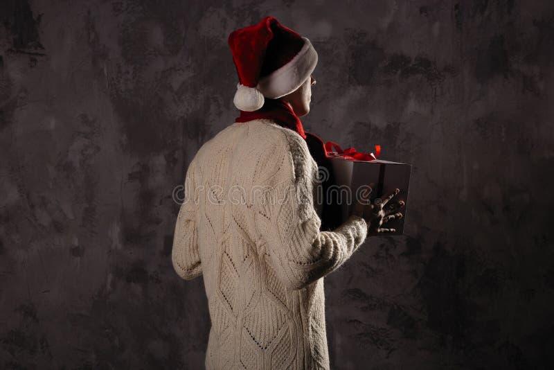 Bożenarodzeniowy prezenta pojęcie Mężczyzna w Santa kapeluszu przynosi prezent dla ciebie Att fotografia royalty free