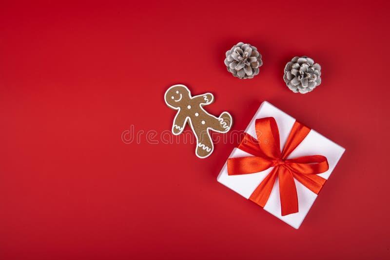 Bożenarodzeniowy prezenta pudełko teraźniejszy na czerwonym tle z faborków łękami i świątecznymi wakacyjnymi dekoracjami Horyzont fotografia stock