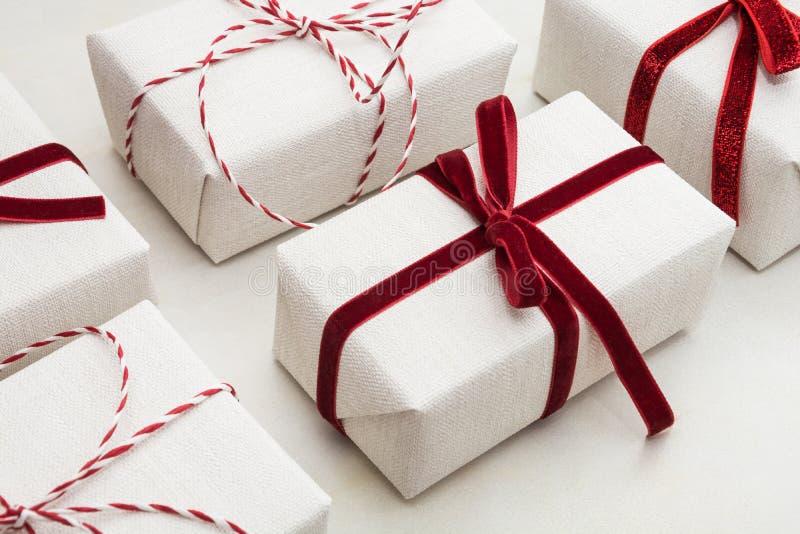 Bożenarodzeniowy prezenta pudełko zawijający w białym papierze i dekoracyjnym czerwonej arkany faborku na marmoreal powierzchni _ obrazy royalty free