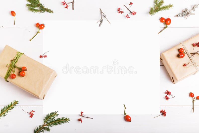 Bożenarodzeniowy pusty kartka z pozdrowieniami w ramie jodła rozgałęzia się, czerwone jagody, prezentów pudełka i rożki nad biały obrazy royalty free