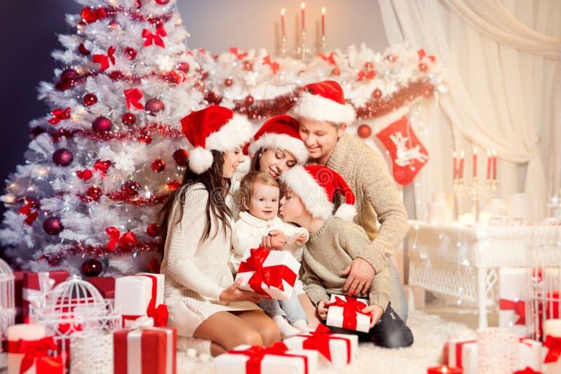 Bożenarodzeniowy rodzina przód Xmas otwarcia teraźniejszości Drzewni prezenty, Szczęśliwi ojciec matki dzieci zdjęcia stock