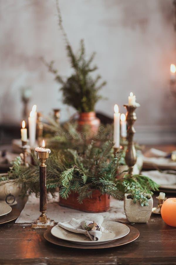 Bożenarodzeniowy Rodzinny Obiadowego stołu pojęcie Świeczki, roczników naczynia, jedlinowe gałąź z jasną kopii przestrzenią na śc obrazy stock