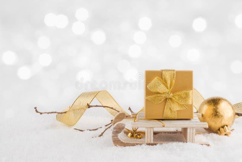 Bożenarodzeniowy sanie z prezentem na śniegu nad abstraktem zaświeca tło zdjęcia stock