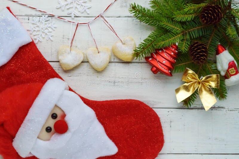 Bożenarodzeniowy skład: buty dla prezentów, dekoraci jodły gałąź z jaskrawymi zabawkami, torty w postaci serca zdjęcie stock