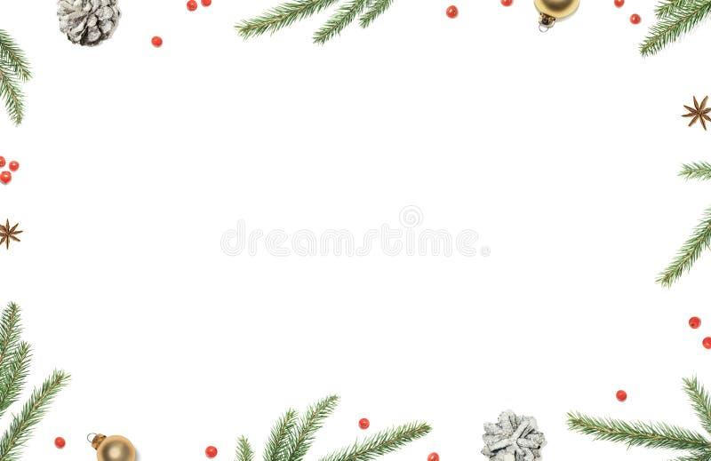 Bożenarodzeniowy skład z choinek gałąź, dekoracjami, czerwonymi jagodami i sosna rożkiem, obramiał białego tło, odgórny widok zdjęcia stock