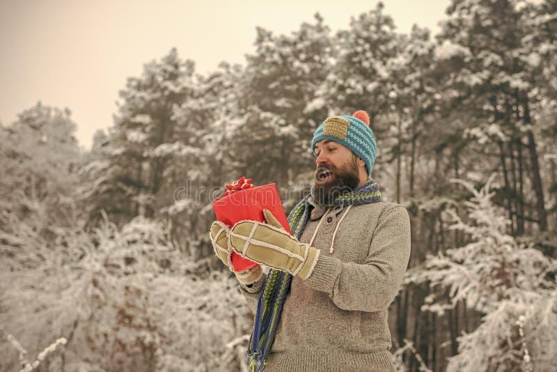 Bożenarodzeniowy szczęśliwy mężczyzna z broda chwyta teraźniejszości pudełkiem fotografia stock