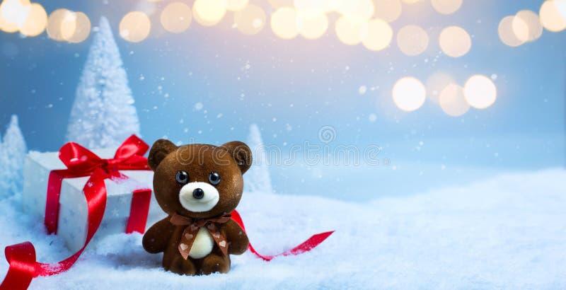 Bożenarodzeniowy sztandaru tło; Choinka, śliczny miś i prezenta pudełko na śniegu, obrazy royalty free