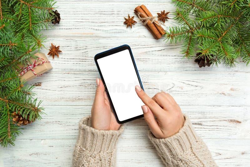 Bożenarodzeniowy tło: kobieta wręcza przesyłanie wiadomości smartphone na nieociosanym drewnianym stołowym tle z Bożenarodzeniową zdjęcia stock