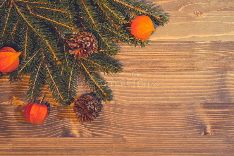 Bożenarodzeniowy tło od naturalnych materiałów - choinek gałąź, rożki, lampiony pęcherzyca na drewnianym fotografia stock