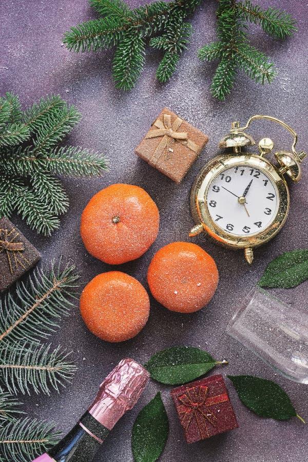Bożenarodzeniowy tło, tangerines, prezenty, szampan, budzik zakrywa z śniegiem Purpurowy tło, odgórny widok zdjęcie stock