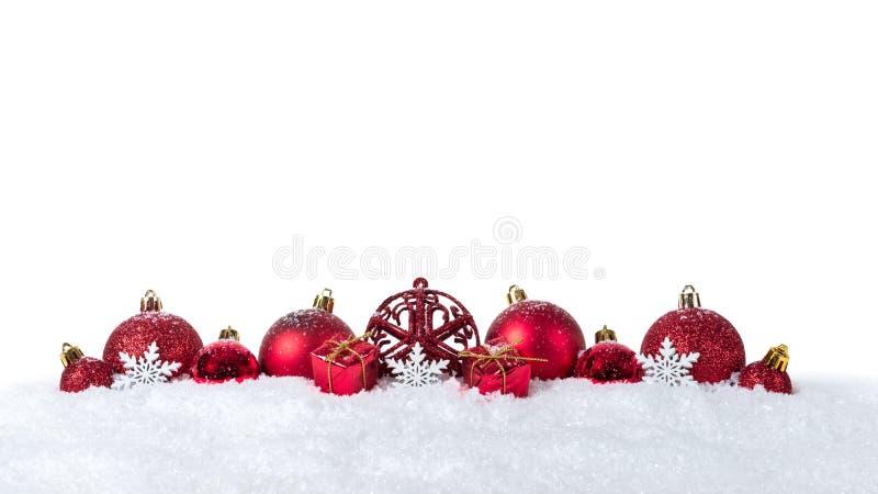 Bożenarodzeniowy tło z dekoracjami i boże narodzenie piłkami na śniegu odizolowywającym na białym tle fotografia stock