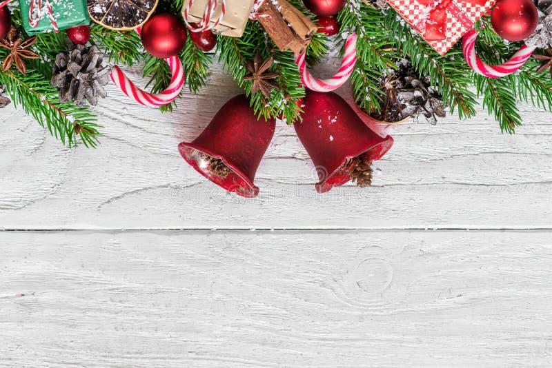 Bożenarodzeniowy tło z jedlinowym drzewem, boże narodzenie dzwonami, cukierkiem, prezentów pudełkami, jagodami i sosną, konusuje  zdjęcie stock