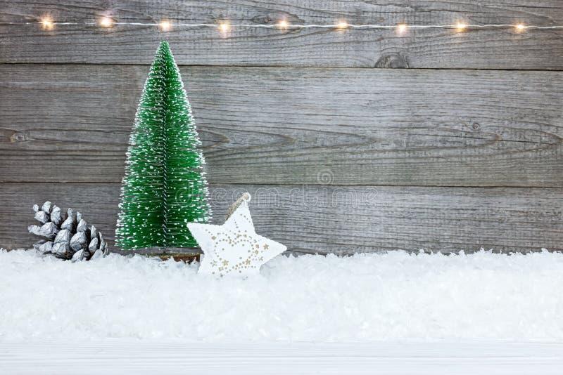 Bożenarodzeniowy tło z jedlinowym drzewem, gwiazdą, sosna rożkiem dalej i śniegiem, zdjęcie royalty free