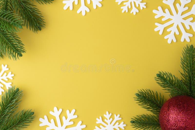 Bożenarodzeniowy tło z jodeł gałąź, zabawkarska czerwona piłka lub bauble mieszkanie, płatek śniegu i nowego roku kłaść na żółtym fotografia stock